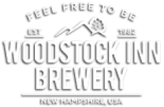 Outline of a Mountain with white letters underneath that spell Woodstock Inn Brewery